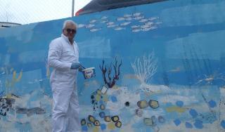 Abel Brčić ispred murala koji je oslikao sa svojim učenicima iz OŠ Petra Kanavelića, Korčula, 2016.